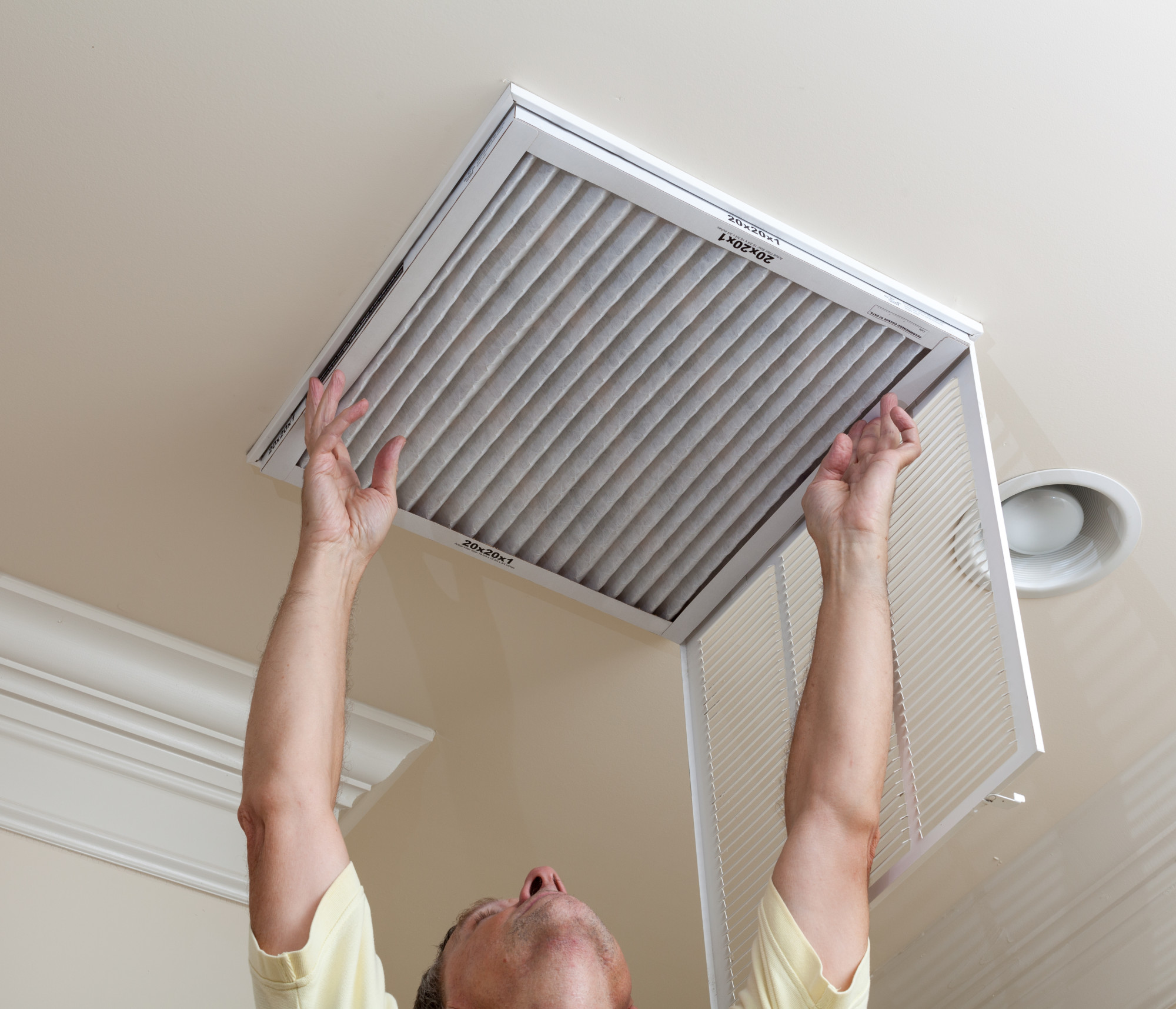 man replacing HVAC filter